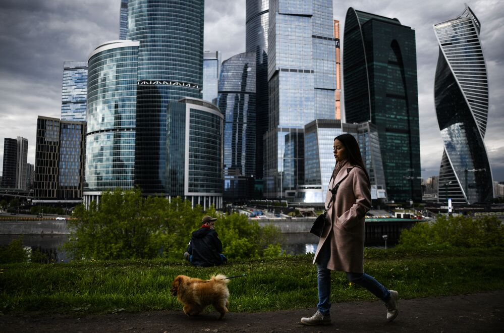 A girl walking with a dog on the Taras Shevchenko embankment in Moscow.