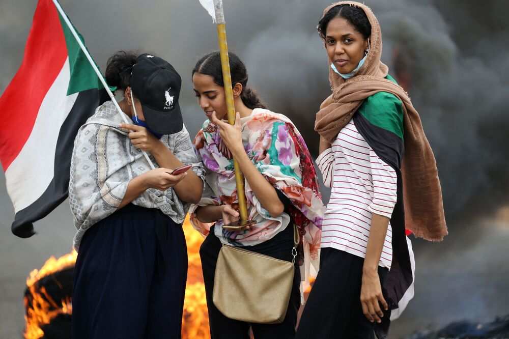Sudanese women lift national flags by burning tyres as they take part in a demonstration on Sixty Street in the capital Khartoum, on 23 May 2020, to commemorate the first anniversary of a deadly crackdown carried out by security forces on Sudanese protesters during a sit-in outside army headquarters in the capital,  with a death toll of over a 100.