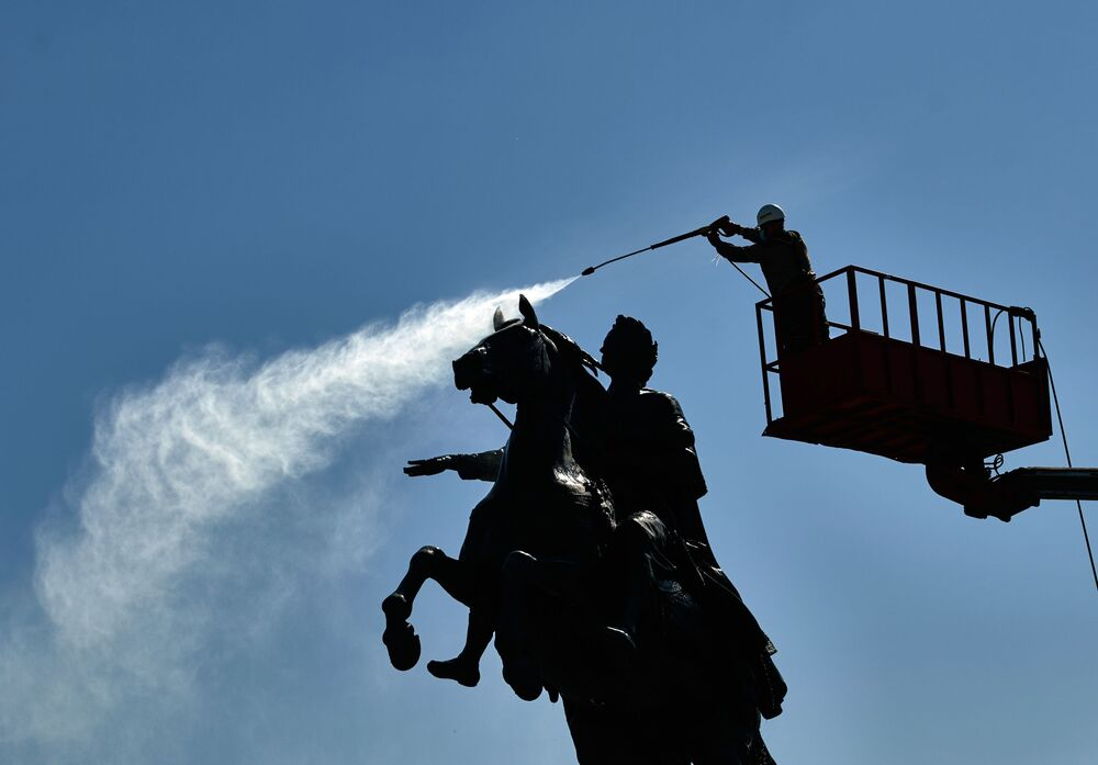 Worker while washing a monument to Peter I on Senate Square in St. Petersburg.