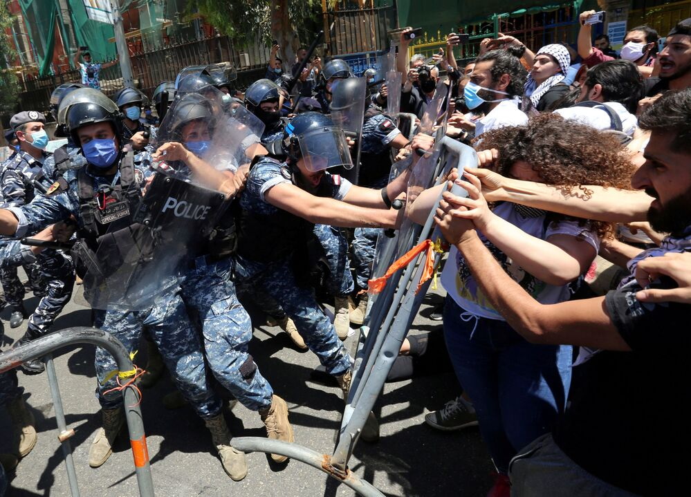 Demonstrators confront with riot police as they try to cross barricades on a road leading to the UNESCO Palace where Lebanon's parliament is holding a legislative session, during a protest against a controversial amnesty draft law, in Beirut Lebanon 28 May 2020.
