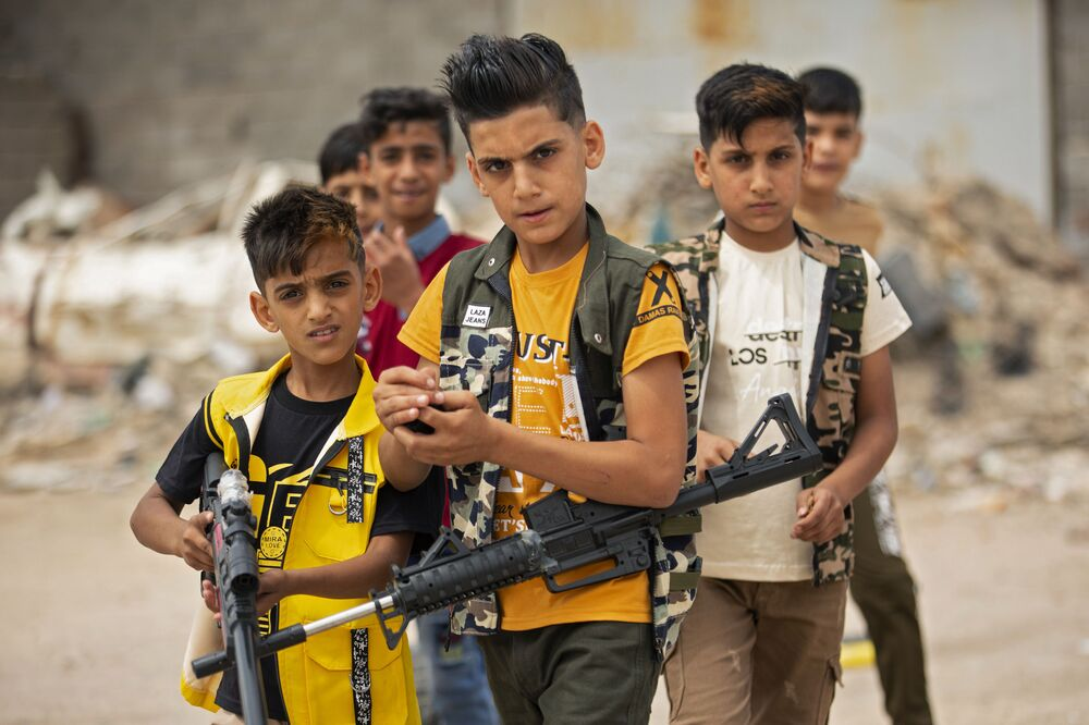 Iraqi children play with plastic toy guns as they celebrate Eid al-Fitr, the Muslim holiday which starts at the conclusion of the holy fasting month of Ramadan, in the southern Iraqi city of Basra on 25 May 2020. Muslims around the world began marking a sombre Eid al-Fitr, many under coronavirus lockdown, but lax restrictions offered respite to worshippers in some countries despite fears of skyrocketing infections.