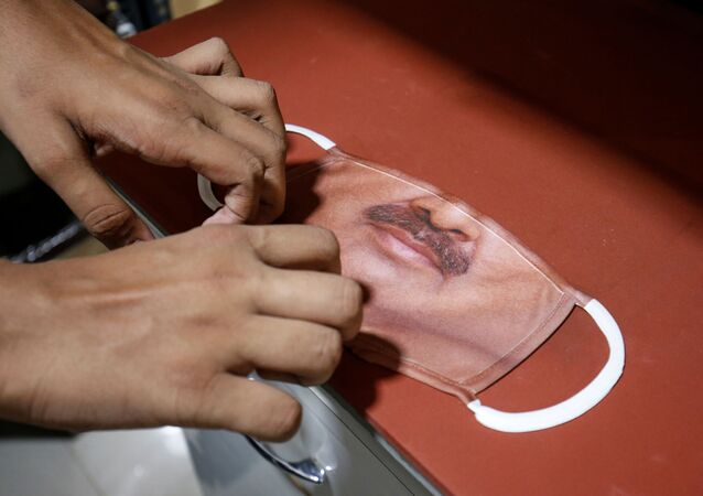 A man prepares a face mask with the photograph of a customer printed on it, amid the spread of the coronavirus disease (COVID-19), at a photo studio in Gandhinagar, India, May 27, 2020.