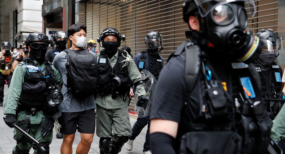 Riot police officers detain an anti-government demonstrator during a protest at Central District against the second reading of a controversial national anthem law in Hong Kong, China May 27, 2020. REUTERS