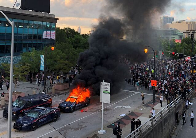 An Atlanta Police car burns as people protest against the death in Minneapolis police custody of African-American man George Floyd, near CNN Center in Atlanta, Georgia, U.S. May 29, 2020.