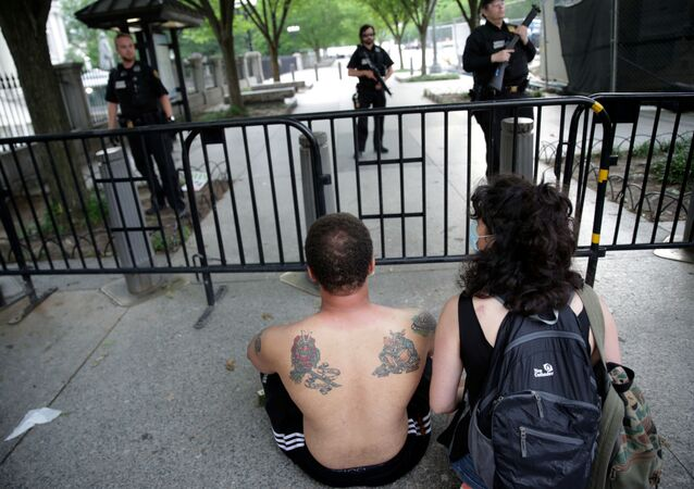 A man sits and faces down US Secret Service uniformed division officers after being pepper sprayed by officers as demonstrators tried to get near the White House during a rally and march against the death in Minneapolis police custody of African-American man George Floyd, in Lafayette Park in Washington, DC. 29 May 2020.