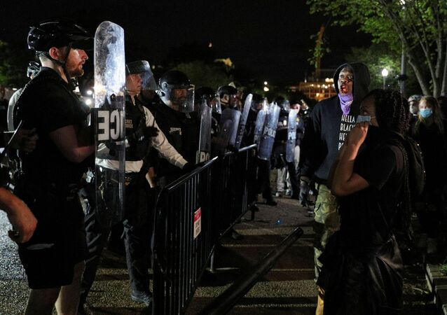 A protestor bleeds from the mouth after accidentally hitting himself in the mouth with a barricade while confronting U.S. Secret Service uniformed division officers maintaining a perimeter around the White House after midnight as a crowd of protestors continue to demonstrate against the death in Minneapolis police custody of African-American man George Floyd, in Lafayette Park in Washington, U.S. May 30, 2020.