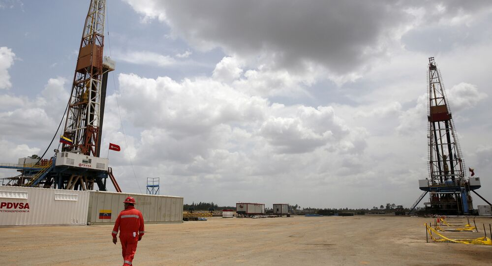 An oilfield worker walks next to drilling rigs at an oil well operated by Venezuela's state oil company PDVSA, in the oil rich Orinoco belt, near Morichal at the state of Monagas April 16, 2015.