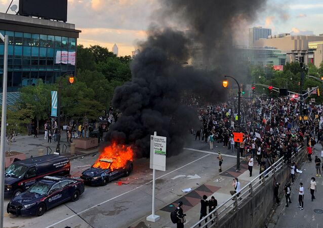 An Atlanta Police car burns as people protest against the death in Minneapolis police custody of African-American man George Floyd