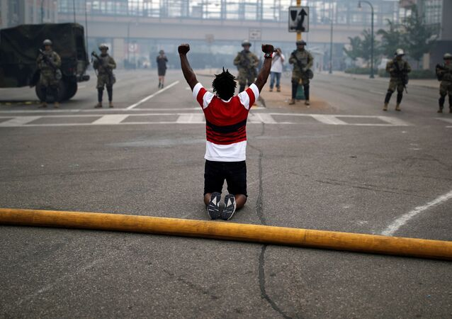 A man reacts as he confronts National Guard members guarding the area in the aftermath of a protest after a white police officer was caught on a bystander's video pressing his knee into the neck of African-American man George Floyd
