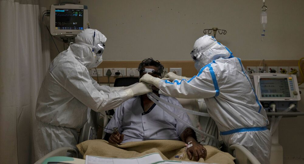 Medical workers wearing PPE take care of a patient suffering from COVID-19, at a hospital in New Delhi
