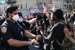 A NYPD police officer sprays protesters as they clash during a march against the death in Minneapolis police custody of George Floyd, in the Brooklyn borough of New York City, U.S., May 30, 2020.