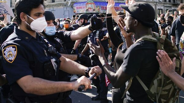 A NYPD police officer sprays protesters as they clash during a march against the death in Minneapolis police custody of George Floyd, in the Brooklyn borough of New York City, U.S., May 30, 2020. - Sputnik International