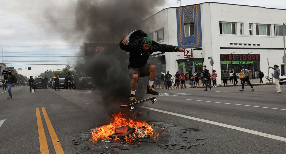 A man jumps with a skateboard over fire during a protest against the death in Minneapolis police custody of George Floyd, in Los Angeles, California, U.S., May 30, 2020.