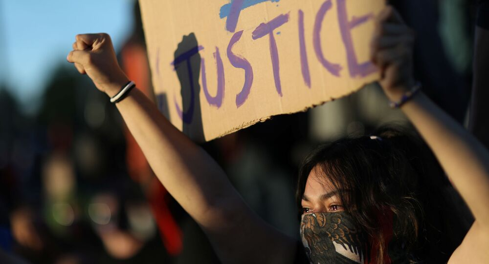 A protester holds a sign as protesters continue to rally against the death in Minneapolis police custody of George Floyd, in Minneapolis, Minnesota, U.S. May 30, 2020.