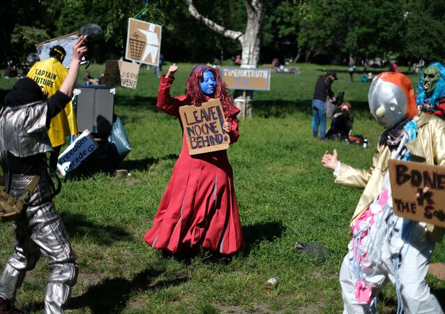 Dressed-up counter protestors pose with signs as people demonstrate against the government's restrictions following the coronavirus disease (COVID-19) outbreak, at Mauerpark in Berlin, Germany, May 30, 2020.