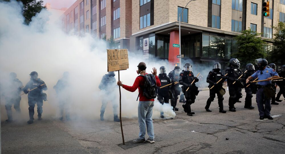 A protester faces riot police advancing through tear gas during nationwide unrest following the death in Minneapolis police custody of George Floyd, in Raleigh, North Carolina, US.