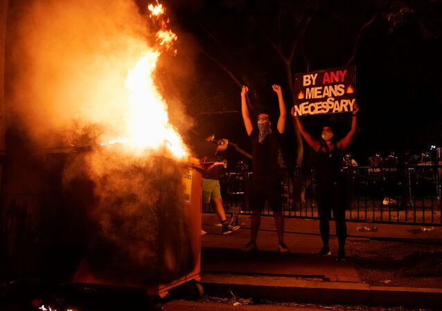 Demonstrators gesture and hold a sign next to a fire during a rally near the White House against the death in Minneapolis police custody of George Floyd in Washington, D.C. U.S. May 30, 2020.