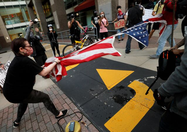 Protesters rip apart a US flag during nationwide unrest following the death in Minneapolis police custody of George Floyd, in Raleigh, North Carolina, US.