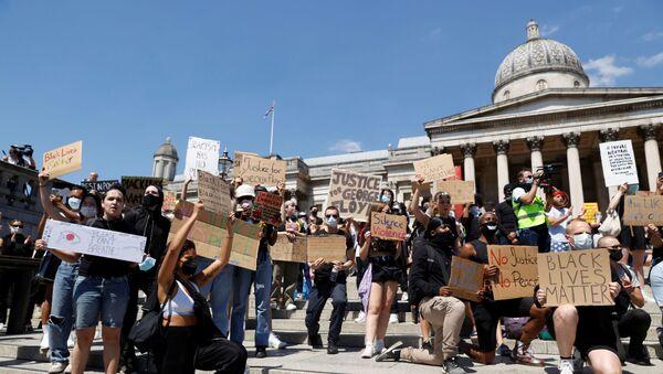 People holds signs during a protest in Trafalgar Square - Sputnik International