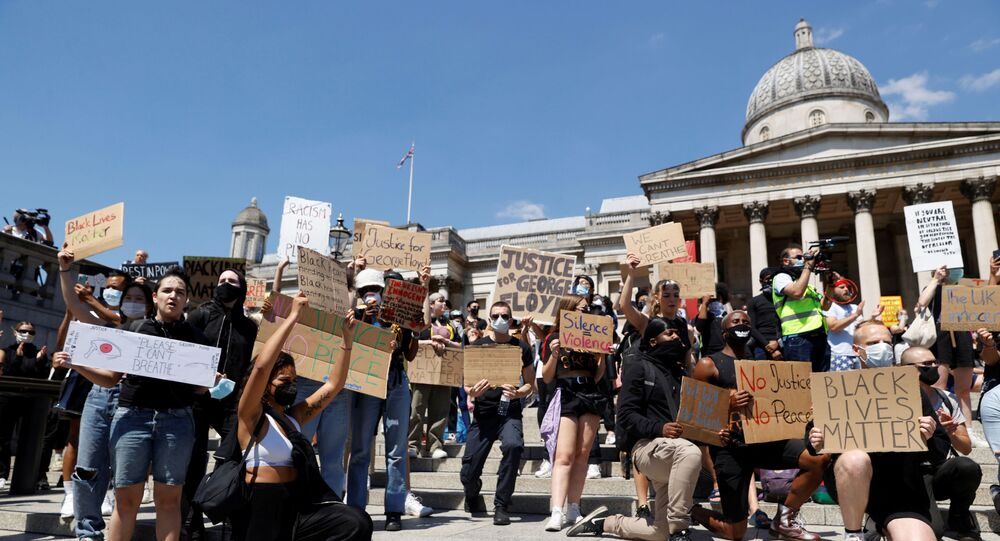 People holds signs during a protest in Trafalgar Square