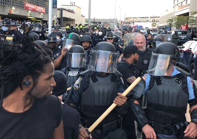 Riot police hold a line near a damaged Atlanta Police cars as people protest against the death in Minneapolis police custody of African-American man George Floyd, near CNN Center in Atlanta, Georgia, U.S. May 29, 2020