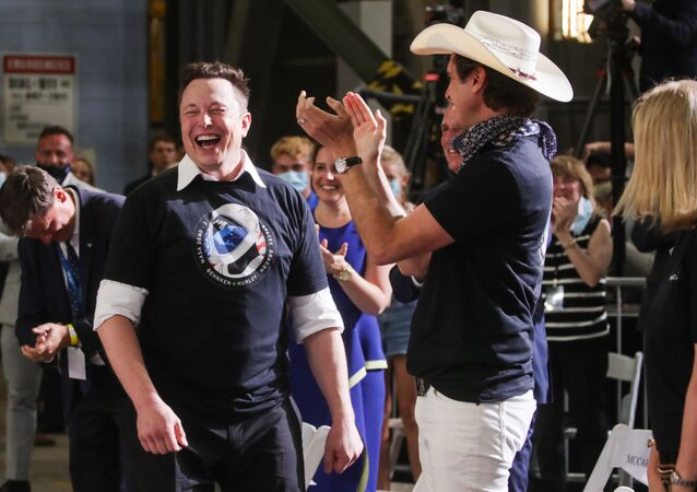 Elon Musk's brother Kimbal Musk applauds to him at a briefing after the launch of a SpaceX Falcon 9 rocket and Crew Dragon spacecraft on NASA's SpaceX Demo-2 mission to the International Space Station from NASA's Kennedy Space Center in Cape Canaveral, Florida, U.S. May 30, 2020.