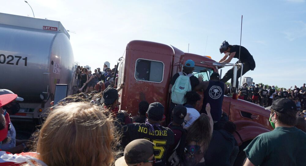 Protesters scale a truck that was driven into a rally  against the death in Minneapolis police custody of George Floyd on the I-35W bridge in Minneapolis, U.S., May 31, 2020.