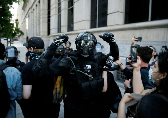 An anarchist reacts to the camera during a protest amid nationwide unrest following the death in Minneapolis police custody of George Floyd, at Lafayette Park near the White House in Washington, U.S., May 31, 2020.