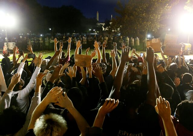 Protesters raise their hands in front of a police line during a protest amid nationwide unrest following the death in Minneapolis police custody of George Floyd, near the White House in Washington, U.S., May 31, 2020.
