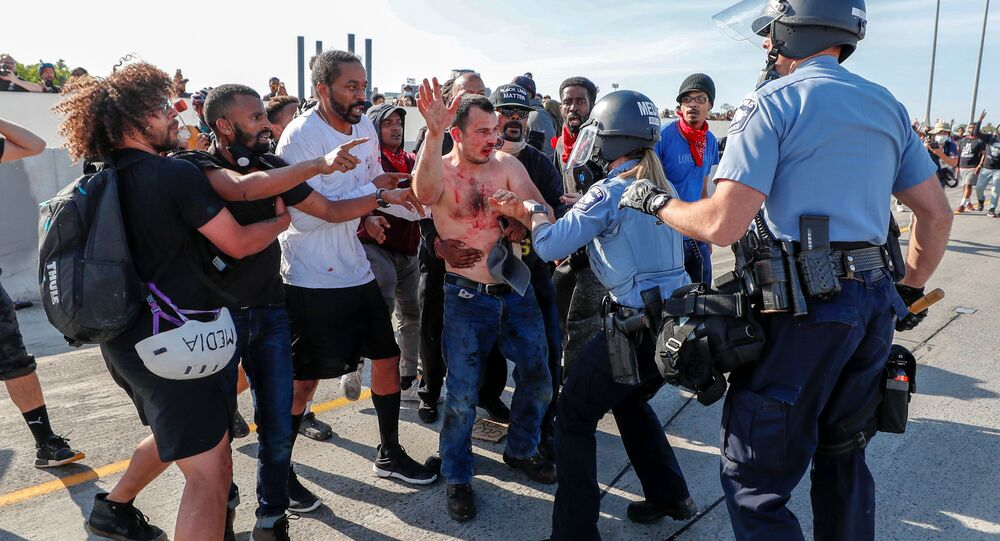 Protesters hand over to police the driver (C) of a tanker truck who drove into hundreds of protesters marching on 35W northbound highway during a protest against the death in Minneapolis police custody of George Floyd, in Minneapolis, Minnesota.