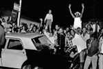 Demonstrators push against a police car after rioting erupted in the Watts district of Los Angeles in 1965.