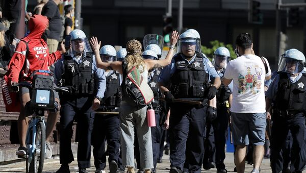 A person raises up their arms while blocking Chicago Police officers during a protest over the death of George Floyd in Chicago, Saturday, May 30, 2020 - Sputnik International