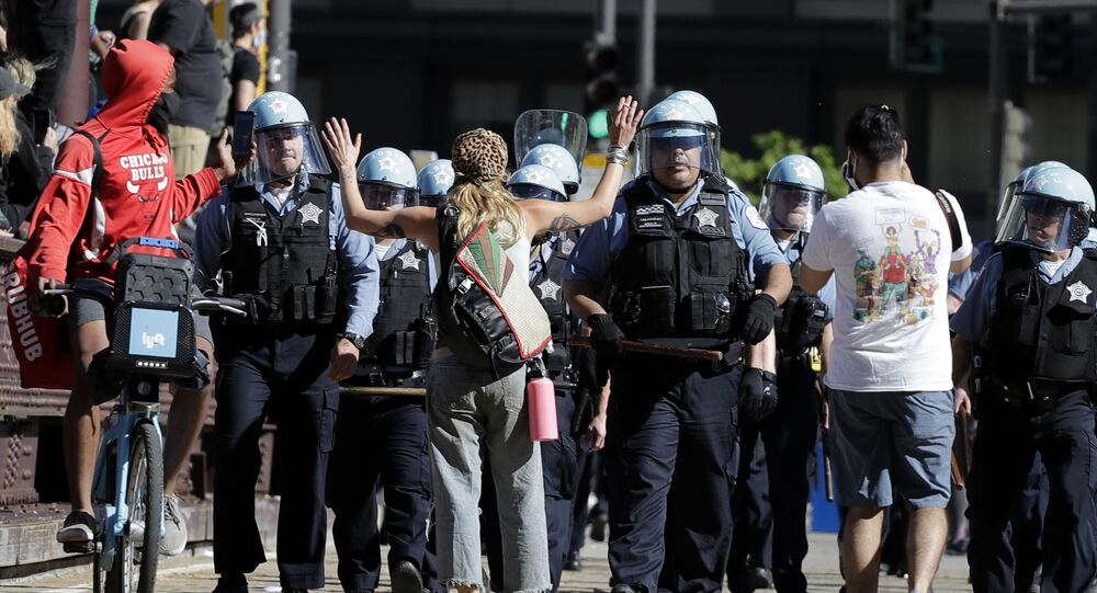 A person raises up their arms while blocking Chicago Police officers during a protest over the death of George Floyd in Chicago, Saturday, May 30, 2020