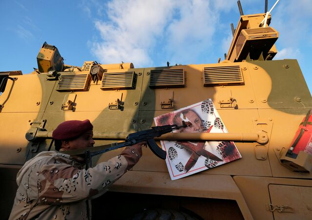 A member of Libyan National Army (LNA) commanded by Khalifa Haftar, points his gun to the image of Turkish President Tayyip Erdogan hanged on a Turkish military armored vehicle, which LNA said they confiscated during Tripoli clashes, in Benghazi, Libya January 28, 2020