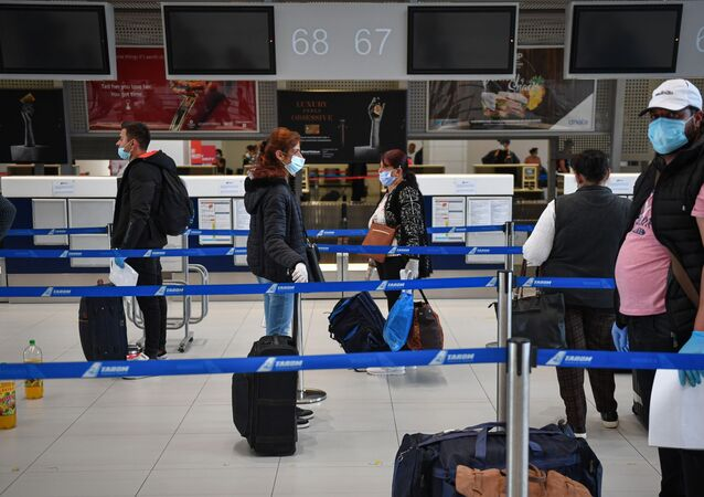 Romanian harvest workers heading to the UK wait in line to enter the Henry Coanda airport in Bucharest April 30, 2020, amid the novel coronavirus COVID-19 pandemic