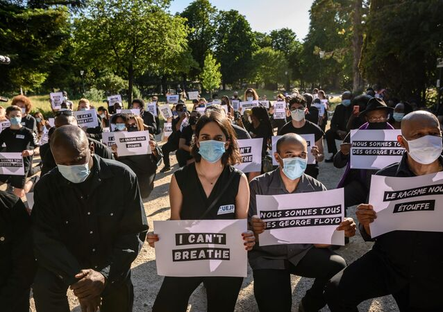 Protesters hold placards including two reading We are all George Floyd (2nd R) and Racism is suffocating us (R) during a demonstration outside the United States Embassy in Paris on June 1, 2020, after the police killing of unarmed black man George Floyd in the USA