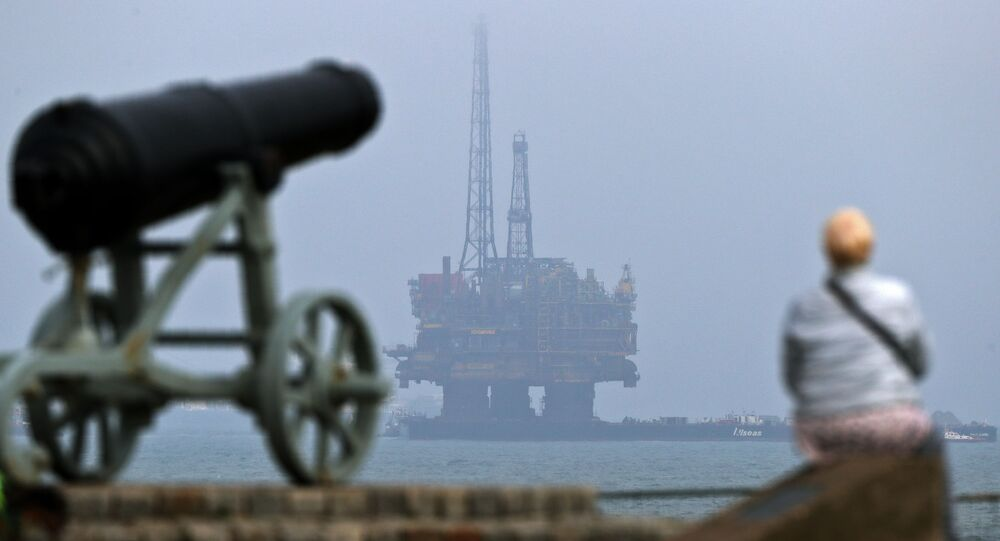A member of the public stands on the shoreline looking out to sea, as Shell's Brent Delta Topside offshore oil drilling rig platform is towed by tug boats off the coast of Hartlepool, north-east England, on May 2, 2017