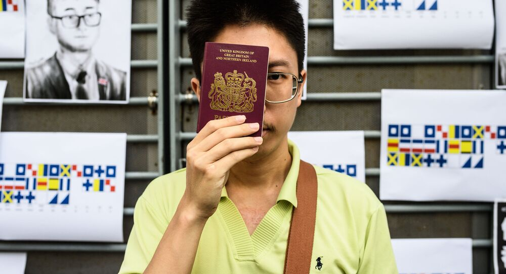 An activist holds a British passport while standing in front of placards carrying a message using International Code of Signals (ICS) flags, during a gathering outside the British Consulate-General building in Hong Kong on August 21, 2019