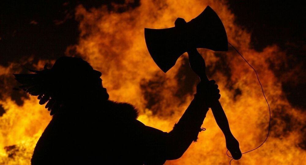 A man dressed as an ancient Viking warrior holds his axe aloft as a Viking Long boat is set alight to mark the traditional start of the New Year celebrations on Carlton Hill, Edinburgh, Scotland, Wednesday Dec. 29, 2004