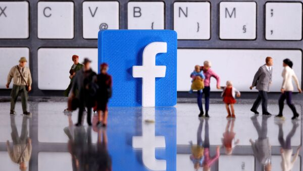 A 3D printed Facebook logo is placed between small toy people figures in front of a keyboard in this illustration taken April 12, 2020 - Sputnik International