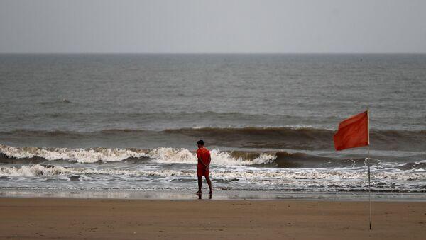 A lifeguard walks along the shore off the Arabian Sea before cyclone Nisarga makes its landfall, in Mumbai, India, June 2, 2020. REUTERS/Francis Mascarenhas - Sputnik International