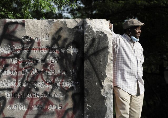Robert Walker poses for a photograph on the remains of a Confederate memorial that was removed overnight in Birmingham, Ala., on Tuesday, June 2, 2020