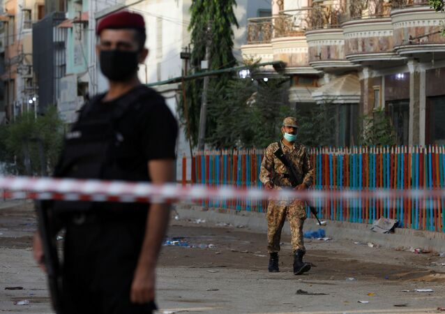 Army soldier walks along a cordoned-off street leading to the site of a passenger plane crash in a residential area near an airport in Karachi, Pakistan May 23, 2020.