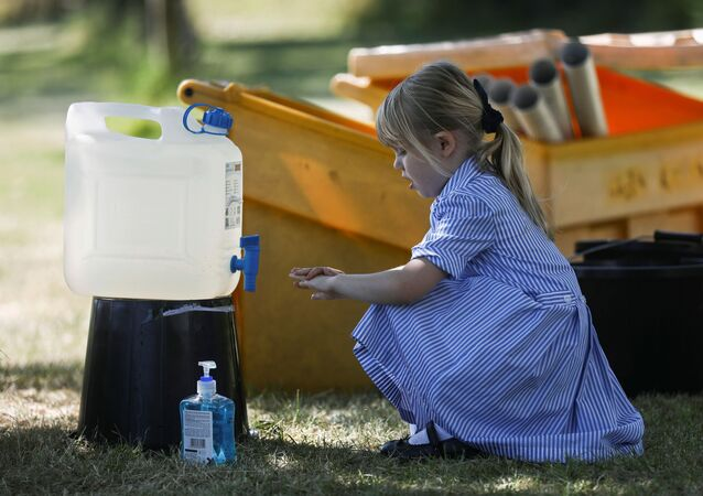 A child washes her hands after playing at St Dunstan's College junior school as some schools re-open following the outbreak of the coronavirus disease (COVID-19) in London, Britain June 1, 2020.