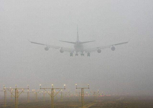 A plane lands at the Indira Gandhi International Airport through morning fog, in New Delhi, India