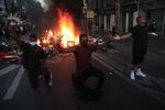 Protesters kneel and react by a burning barricade during a demonstration Tuesday, June 2, 2020 in Paris