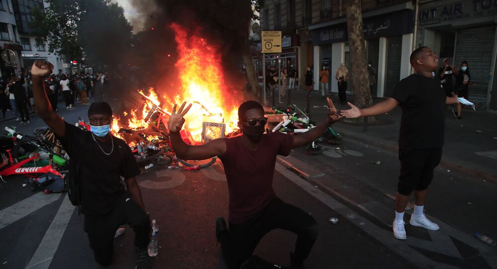 Protesters kneel and react by a burning barricade during a demonstration on 2 June 2020 in Paris