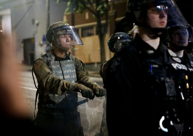 A member of the National Guard leans on his shield behind a line of Seattle police as protesters rally against police brutality and the death in Minneapolis police custody of George Floyd, near the police department's East Precinct location in Seattle, Washington, U.S. June 2, 2020. Picture taken June 2, 2020