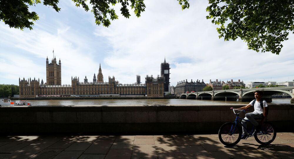 A cyclist passes the houses of the Parliament in London