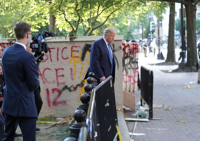 A White House videographer films U.S. President Donald Trump as he walks past a building defaced with graffiti by protestors in Lafayette Park across from the White House after walking to St John's Church for a photo opportunity during ongoing protests over racial inequality in the wake of the death of George Floyd while in Minneapolis police custody, outside the White House in Washington, U.S., June 1, 2020